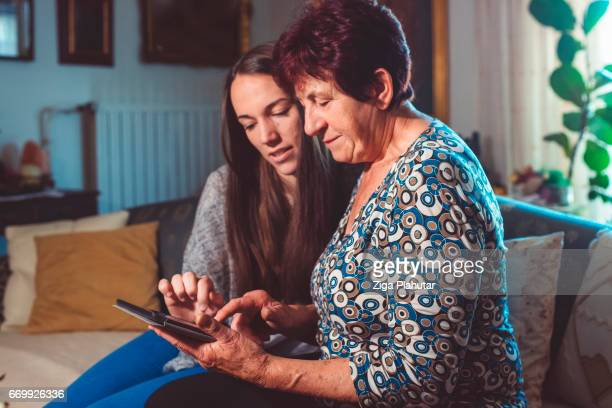Grandchild helping her Grandmother with tablet