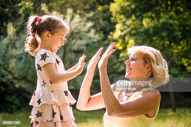 Grandchild playing with grandmother clapping hands