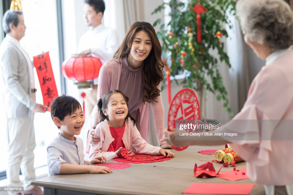 Grandchildren and grandmother with Chinese New Year paper-cut : Stock Photo