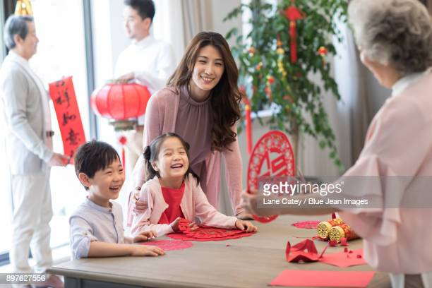 grandchildren and grandmother with chinese new year paper-cut - chinese new year stock pictures, royalty-free photos & images