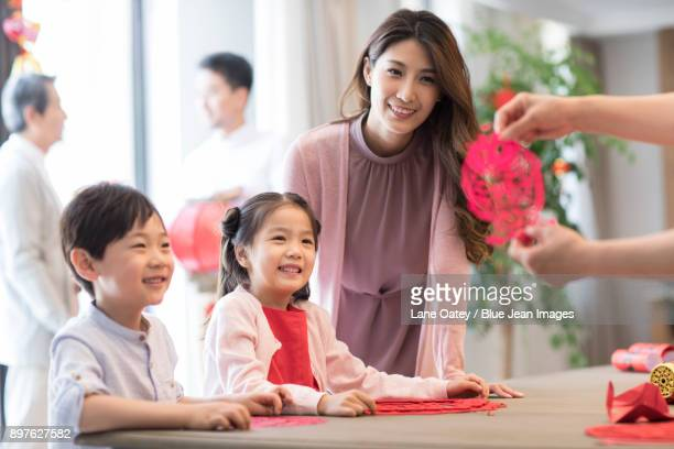Grandchildren and grandmother with Chinese New Year paper-cut