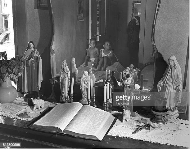 Grandchildren and religious objects in the bedroom of Ella Watson a US government charwoman Washington DC August 1942
