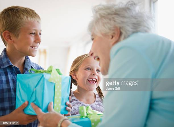 grandchildren giving present to grandmother - birthday present stock pictures, royalty-free photos & images