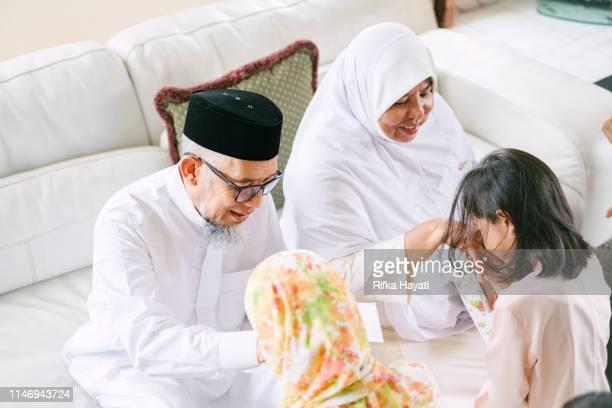 grandchildren taking blessings during festival of hari raya aidilfitri in malaysia - hari raya celebration stock pictures, royalty-free photos & images