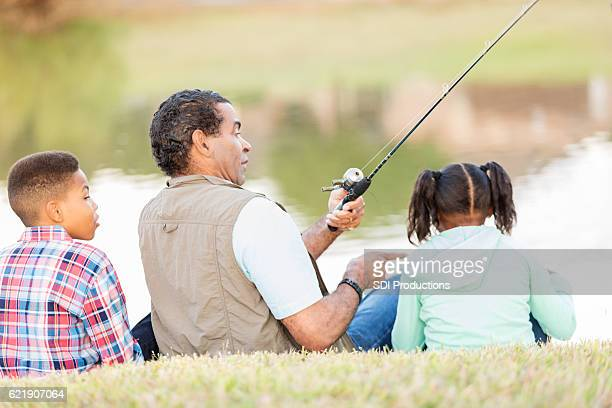 Granddad catches fish while fishing with grandchildren