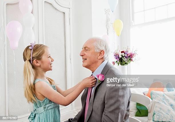 Granddaughter adjusting granddad's tie.