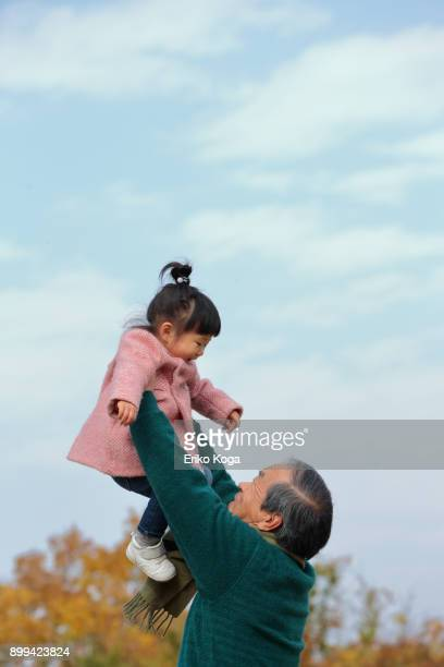 granddaughter and grandfather playing in park - 熊本県 ストックフォトと画像