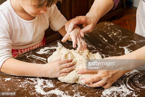 Granddaughter and grandma kneading dough