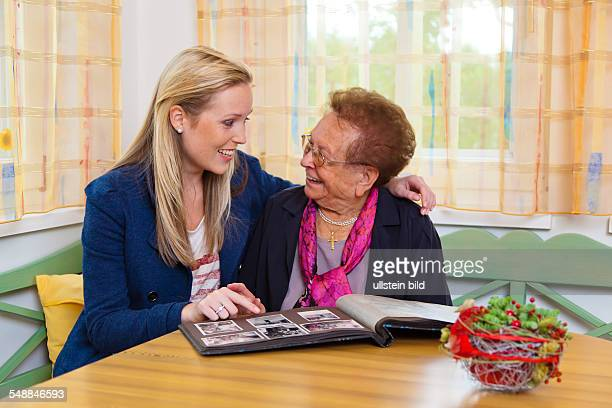 granddaughter and grandmother are looking at a photo album