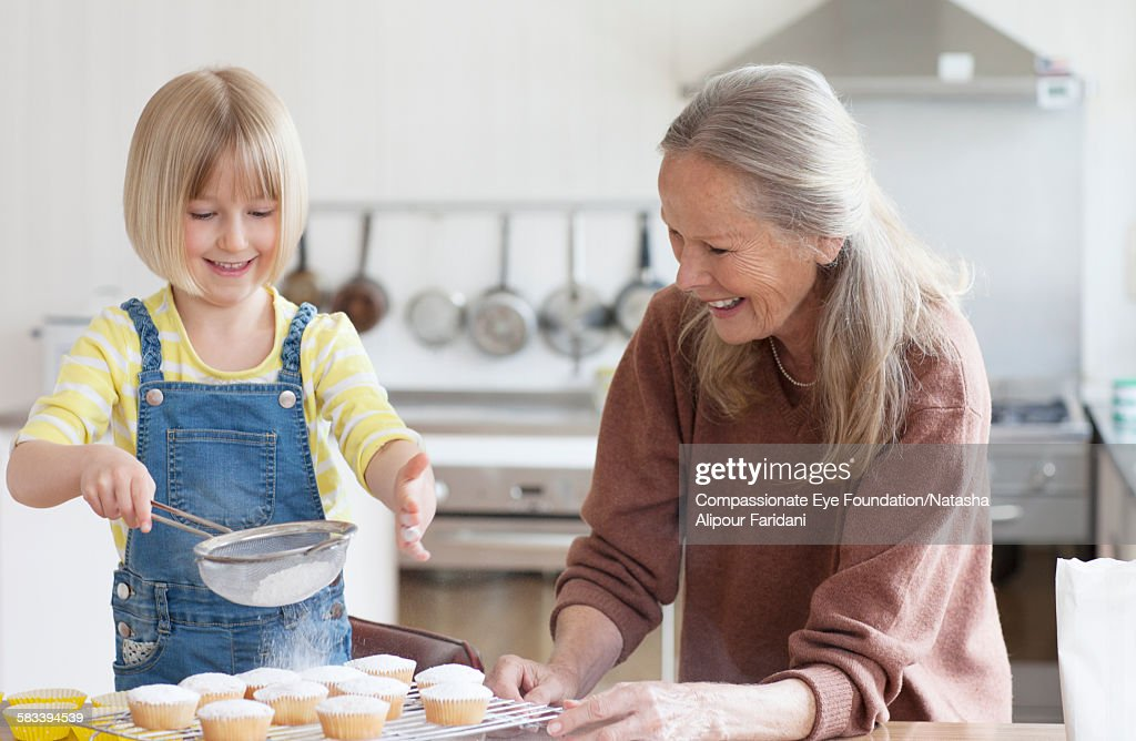 Granddaughter and grandmother baking cakes : Stock Photo