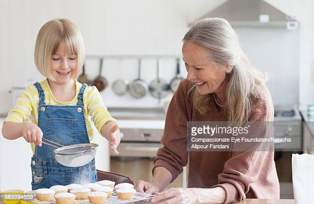 Granddaughter and grandmother baking cakes