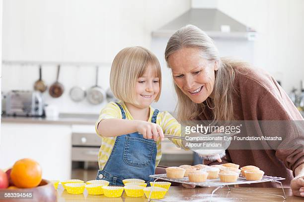 Granddaughter and grandmother baking cupcakes