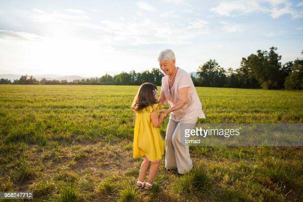 granddaughter and grandmother dancing in nature - grandmother stock pictures, royalty-free photos & images