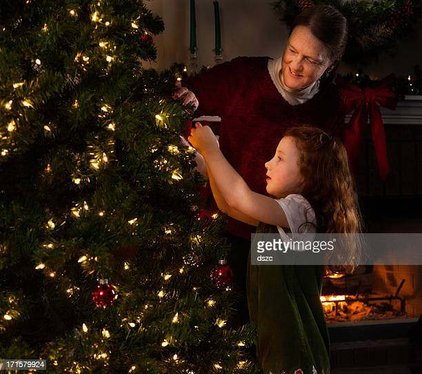 granddaughter and grandmother decorating tree on Christmas eve