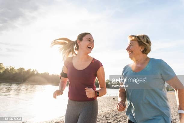 granddaughter and grandmother having fun, jogging together at the river - jung geblieben stock-fotos und bilder