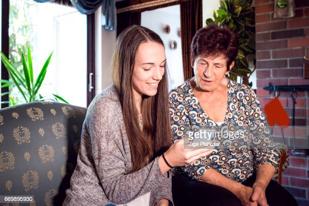 Granddaughter and Grandmother learning how to use smart phone