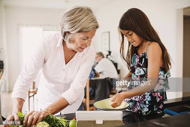 Granddaughter and grandmother preparing food in kitchen