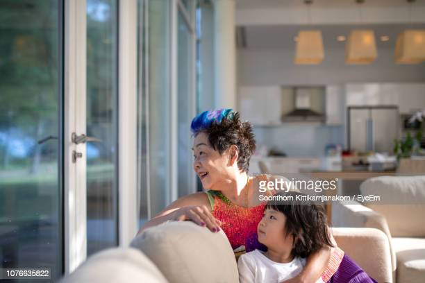 granddaughter and grandmother resting on sofa at home - generation gap stock pictures, royalty-free photos & images