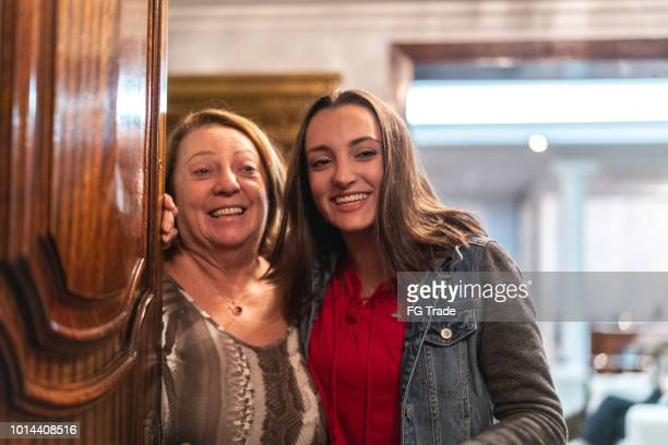 granddaughter and grandmother welcoming home opening his front door - guest stock pictures, royalty-free photos & images