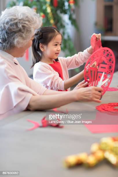 Granddaughter and grandmother with Chinese New Year paper-cut