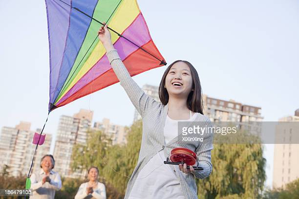 Granddaughter and grandparents with kite in the park