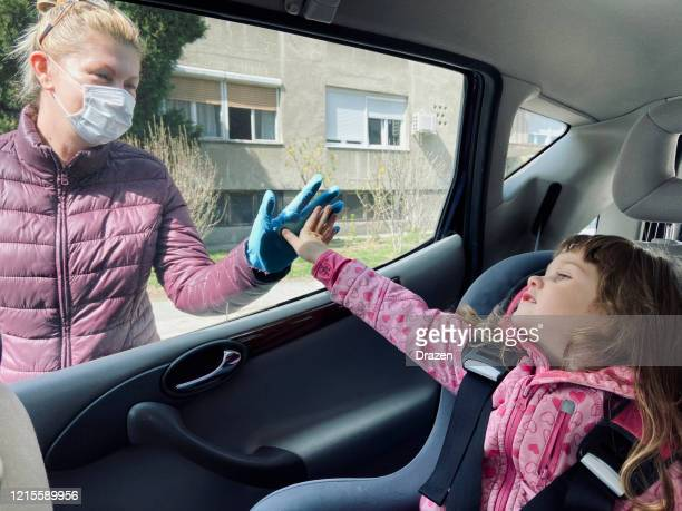 granddaughter and granny saying hi over the car window due to covid-19 social distancing protective measures - shielding stock pictures, royalty-free photos & images