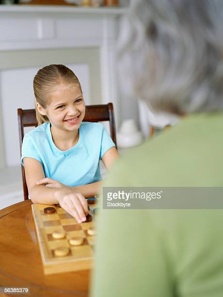 granddaughter and her grandmother playing checkers