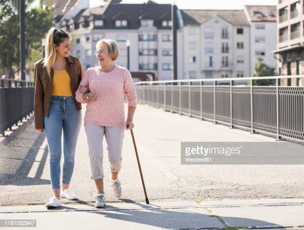granddaughter and her grandmother walking on footbridge - asistir fotografías e imágenes de stock