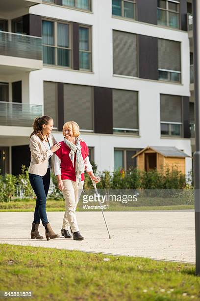 Granddaughter assisting her grandmother walking with crutch