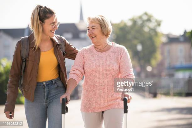 granddaughter assisting her grandmother walking with wheeled walker - mannheim stock-fotos und bilder