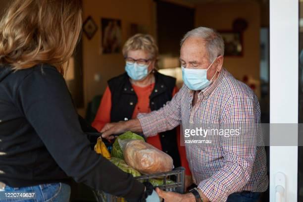nieta llevando las compras a los abuelos durante la pandemia en su casa - compartir fotografías e imágenes de stock