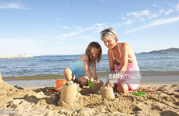 Granddaughter (7-9) building sandcastles with grandmother at beach