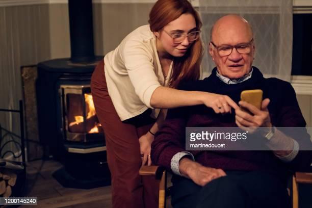 """neta que conecta com o avô sobre um telefone esperto. - """"martine doucet"""" or martinedoucet - fotografias e filmes do acervo"""