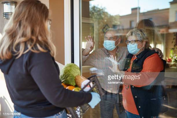 granddaughter delivers groceries to grandparents during pandemic - community care stock pictures, royalty-free photos & images