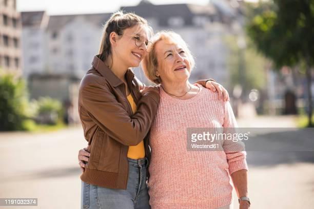 granddaughter embracing her grandmother - nur erwachsene stock-fotos und bilder