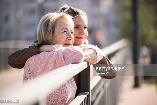 granddaughter embracing her grandmother - mannheim stock-fotos und bilder