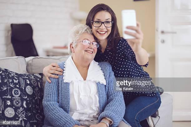 Enkelin umarmen Ihr glückliche Großmutter wie zu Hause fühlen.