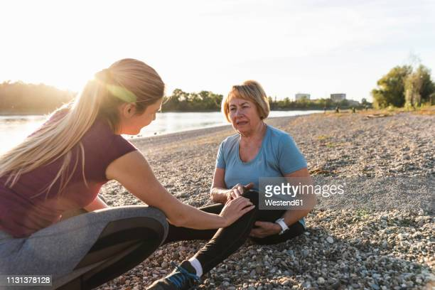 granddaughter examining aching knee of her grandmother after training at the river - knees together stock photos and pictures