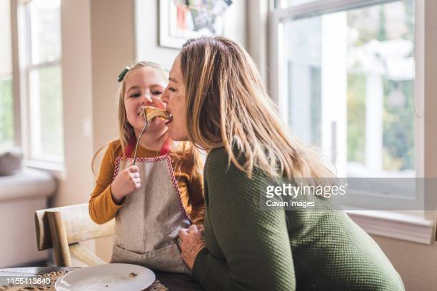 granddaughter feeding pancakes to grandmother at kitchen table - pancakes stock pictures, royalty-free photos & images
