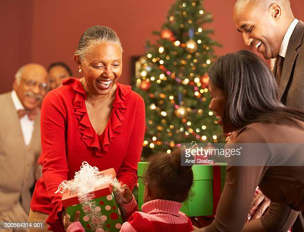 granddaughter (4-5) giving christmas gifts to grandmother - african american christmas images stock pictures, royalty-free photos & images