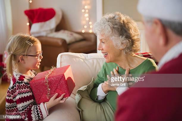 Granddaughter giving Christmas present to Grandma