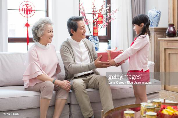 granddaughter giving gift to grandparents during chinese new year - 70 year old man stock pictures, royalty-free photos & images