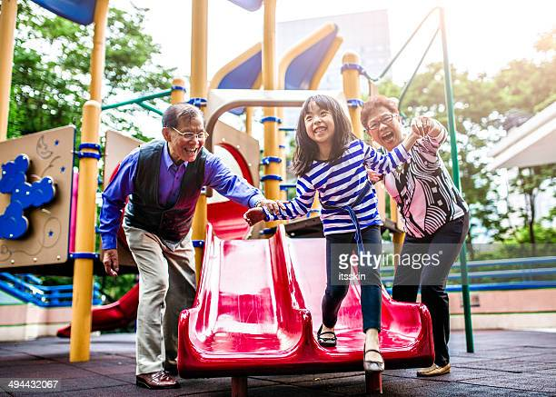 Granddaughter, grandfather and grandmother at playground