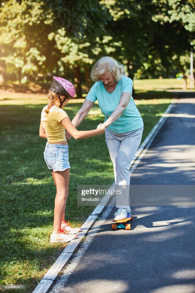 Granddaughter Helping Her Grandmother To Learn How To Ride Skateboard : Foto stock
