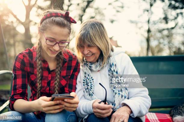 granddaughter helping her grandmother with smartphone setup - granddaughter stock pictures, royalty-free photos & images