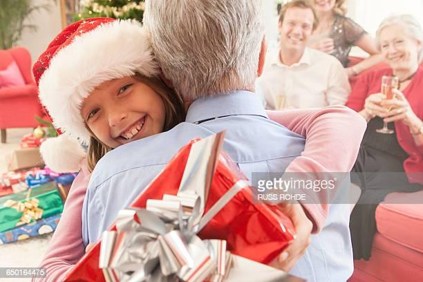 granddaughter holding christmas gift hugging grandfather smiling - 毛皮の飾り ストックフォトと画像