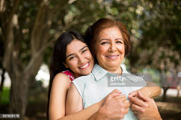 granddaughter holding her grandmother tight - mexican ethnicity stock pictures, royalty-free photos & images