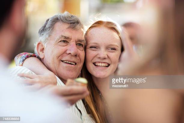 granddaughter hugging grandfather outdoors - party social event stock pictures, royalty-free photos & images
