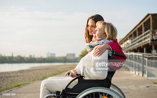 Granddaughter hugging her grandmother sitting in wheelchair