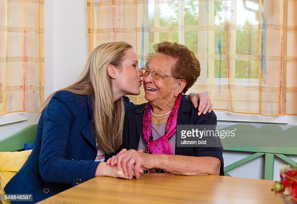 granddaughter is kissing her grandmother